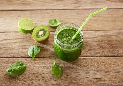 Zielony sok w szklance, obok kiwi, limonka i liście bazylii