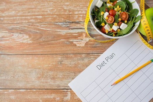 Plan diety z pustymi polami do uzupełnienia, na nim ołówek, obok sałatka w misce, jabłko i centymetr krawiecki