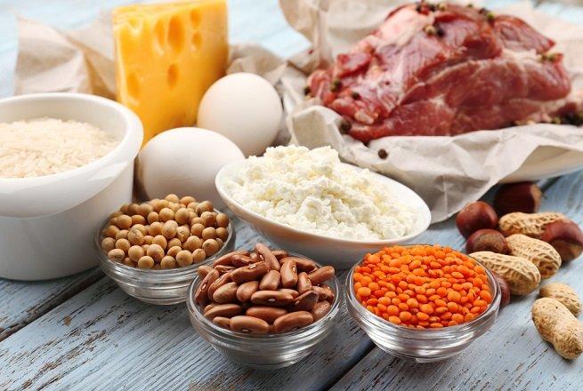 Czerwone mięso, ser żółty, jaja oraz soczewica i ciecierzyca w miseczkach na drewnianym stole