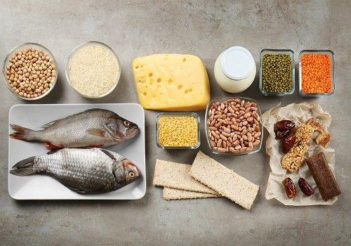 Widok z góry na produkty – ryby na talerzu, ciecierzyca, ser żółty, suszone owoce