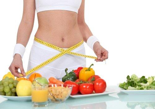 Tułów kobiety sprawdzającej centymetrem krawieckim obwód, przed nią owoce i warzywa na stole
