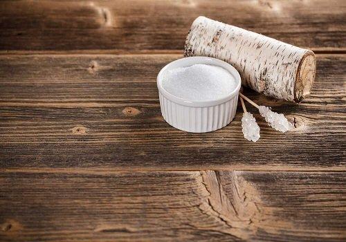 Ksylitol w miseczce na drewnianym stole, obok gałąź brzozy