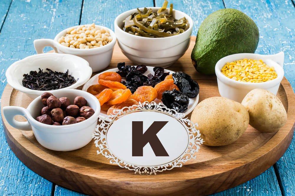 """Awokado, ziemniaki, orzechy i suszone owoce ułożone na drewnianej tacy, przed nią tabliczka z napisem """"K"""""""