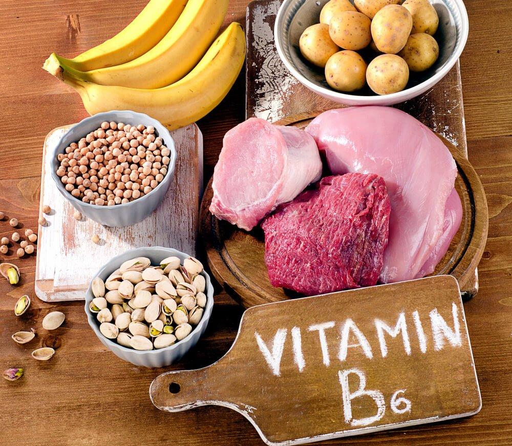 Produkty na drewnianym stole: mięso, ziemniaki, banany, pistacje