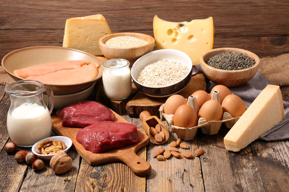 produkty na drewnianym stole: czerwone mięso, jaja, mleko, sery, orzechy