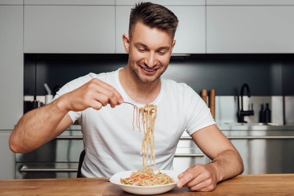 Mężczyzna siedzący przy stole. Trzymający w ręku widelec z makaronem, który ma na talerzu.