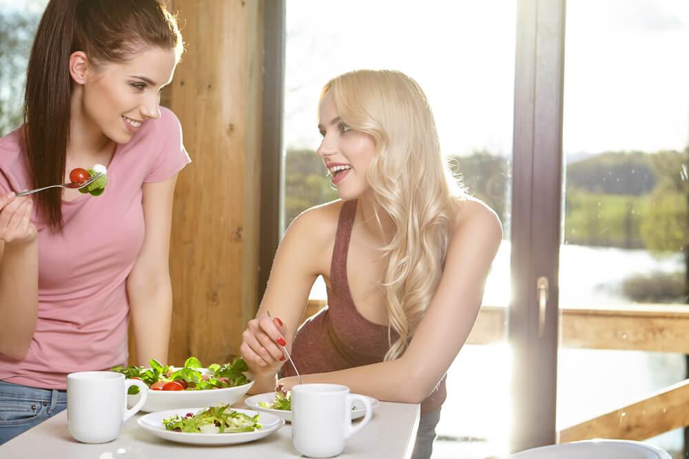 Dwie dziewczyny jedzące sałatkę przy stole