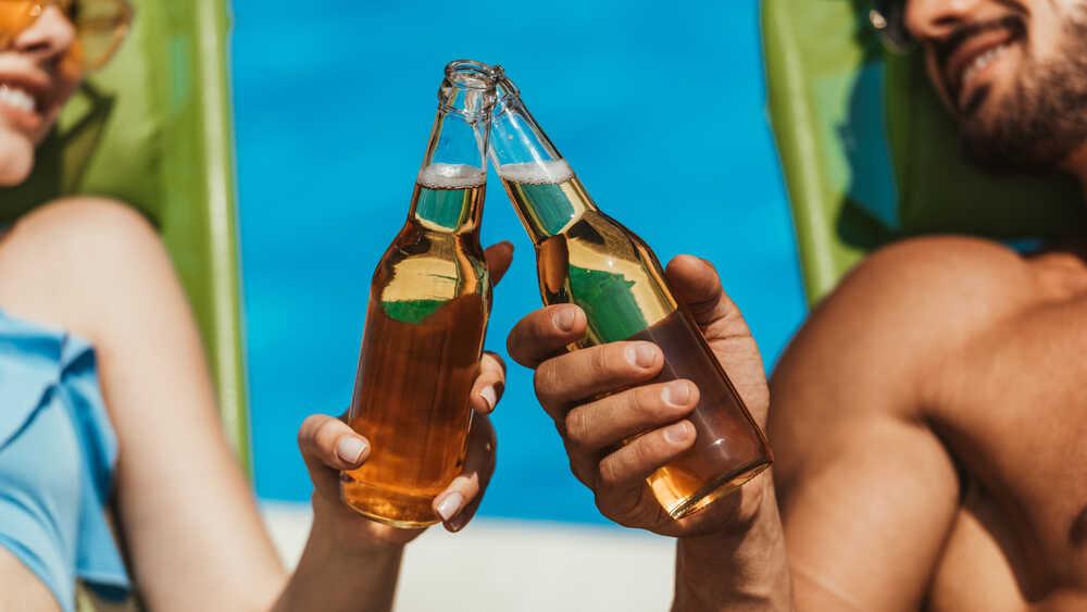 Kobieta i mężczyzna trzymający stukające się butelki z piwem.