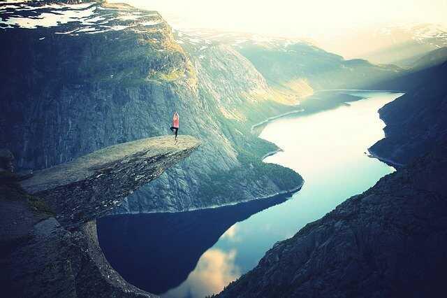 Kobieta ćwicząca jogę na skalę. W tle widok jeziora i gór.