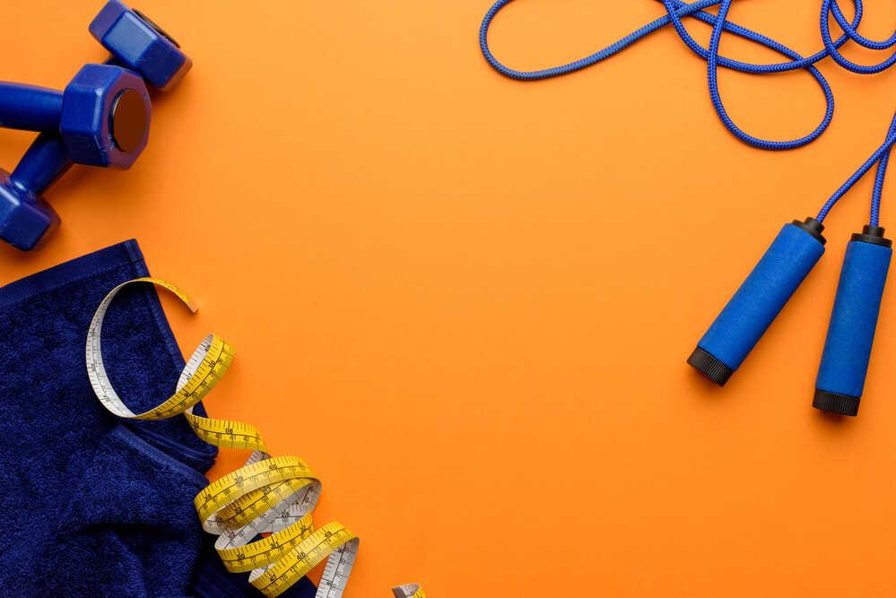 Niebieska skakanka, dwa hantle, ręcznik i miarka krawiecka na pomarańczowym tle.