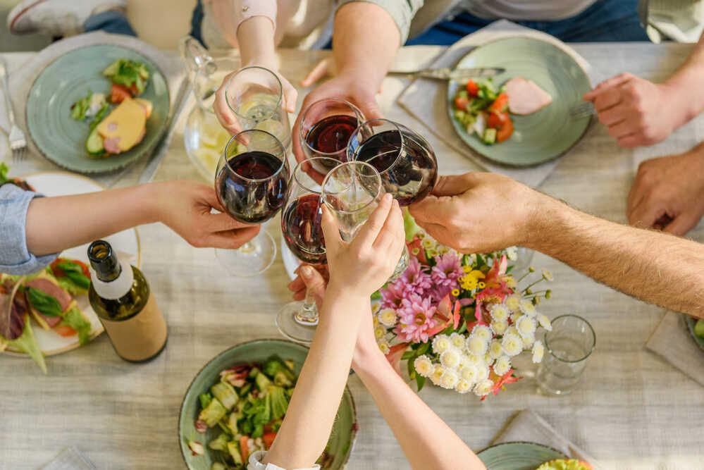 Dłonie, które trzymają stukające się kieliszki z winem, w tle stół z talerzami i potrawami.
