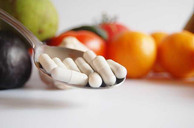 Tabletki na łyczce stołowej, w tle warzywa i owoce.