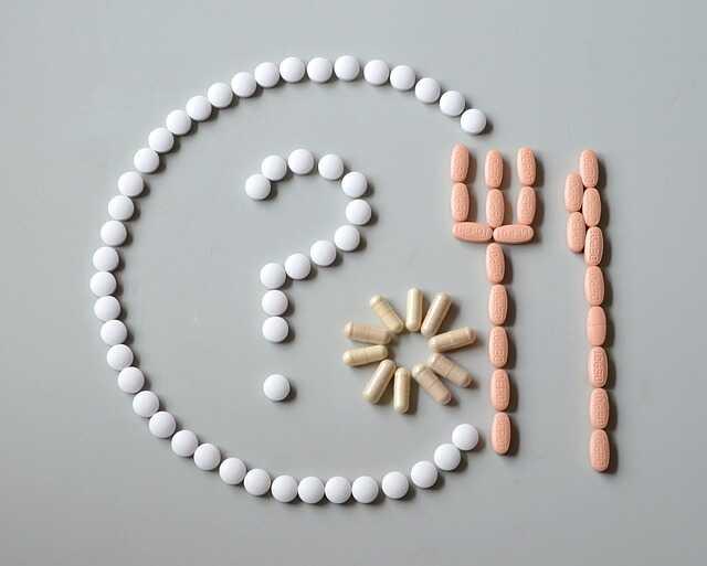 Tabletki ułożone na kształt talerza i sztućców.