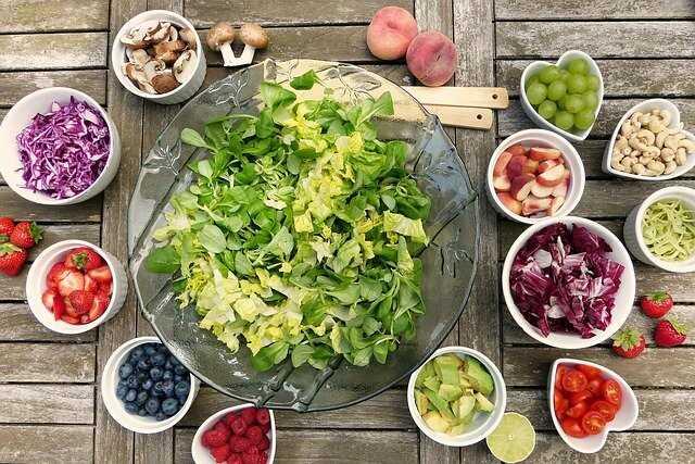 Warzywa, owoce  i orzechy stojące w pojemnikach na drewnianym stole.